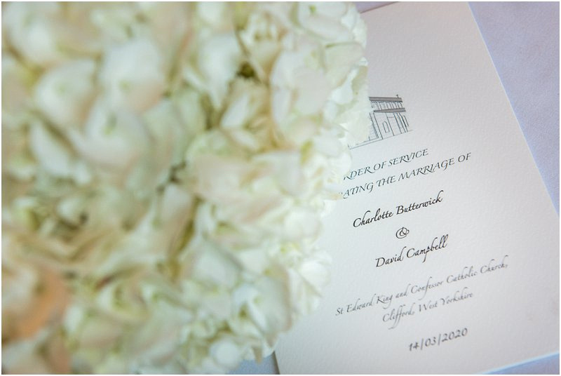 Order of service photographed with wedding bouquet at Hazlewood Castle