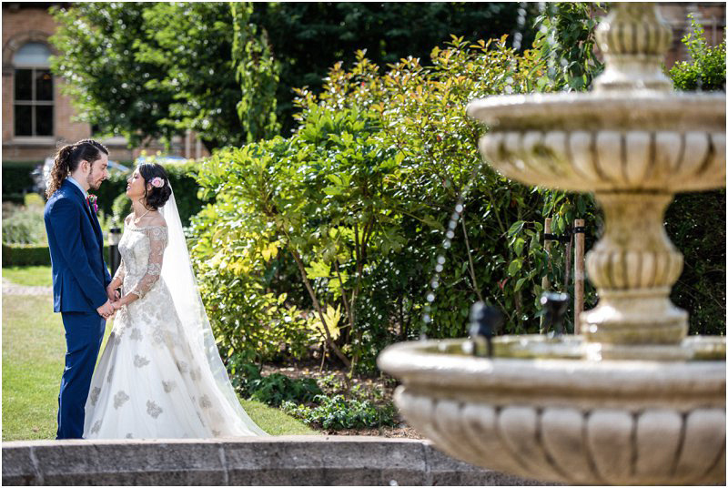 Bride and groom in the gardens holding hands next to a fountain