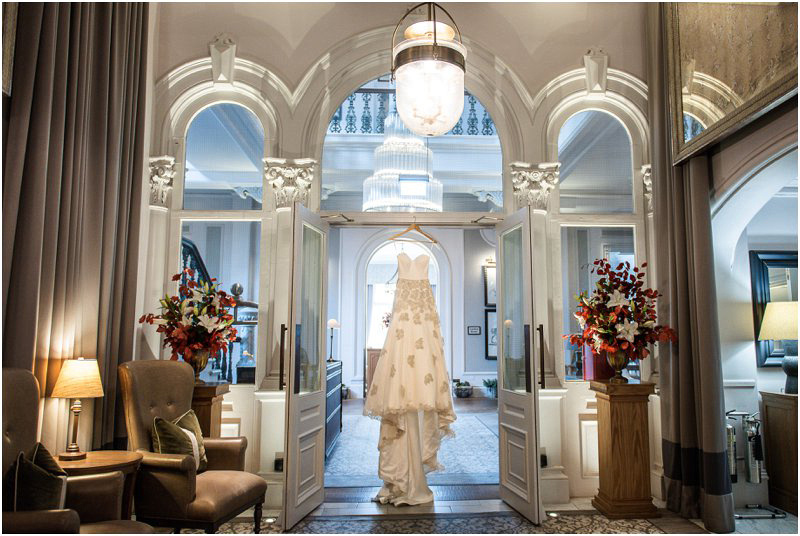 Brides gown hanging majestically in doorway of hotel